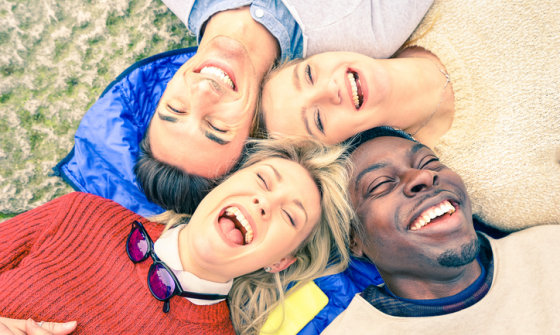 Group of young adults lying down on the grass laughing together