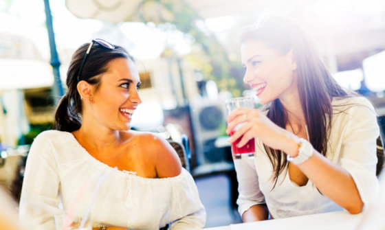 Two young attractive women having fun whilst outside having a drink