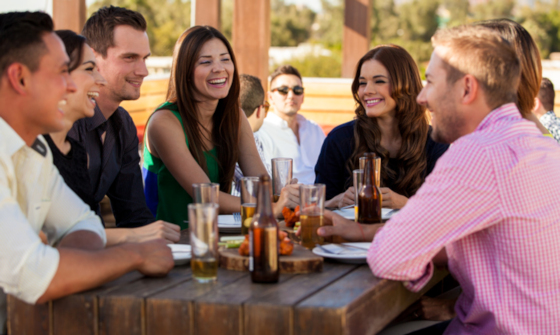 Group of young adults chatting over drinks in a beer garden on a sunny day