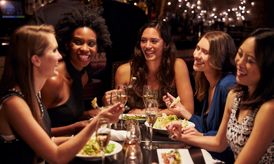 Group of young women chatting over a meal at a trendy restaurant