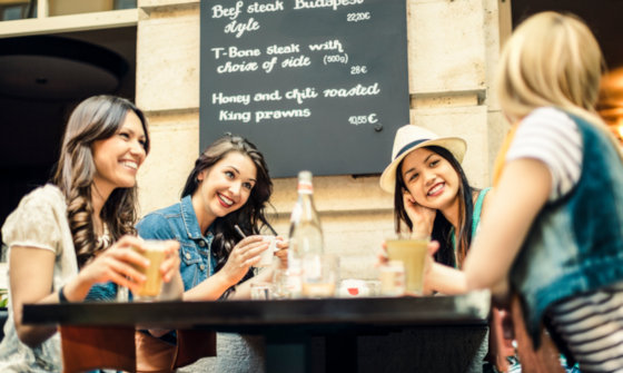 Group of young women chatting over a drink at a trendy bar