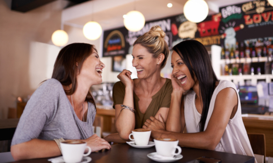Group of young women laughing whilst out for coffee